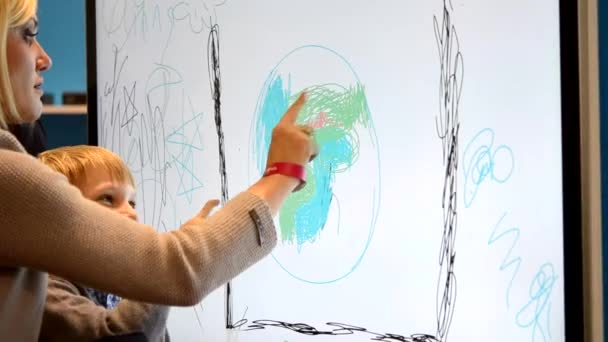 Mother with child draws finger on large monitor touch screen close-up
