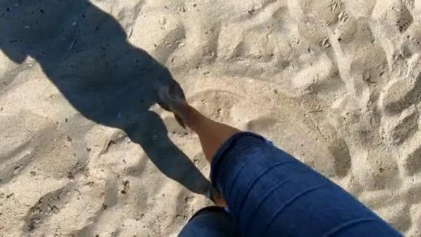 A homokos parton sétáló nő árnyéka