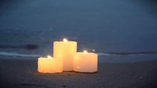 Három kis gyertya a homokos parton, közel a tenger óceán hullámaihoz.