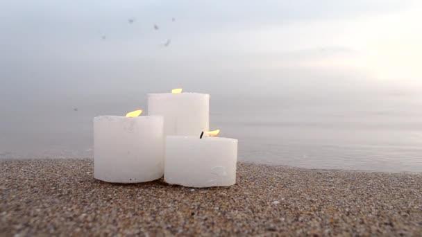 Három kis sárga gyertya a homokos tengerparton, közel a kék óceán hullámaihoz.