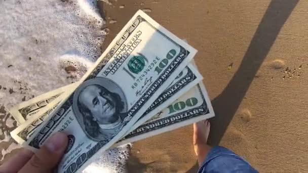 Girl holding money bill of 300 dollars on background of sea ocean waves