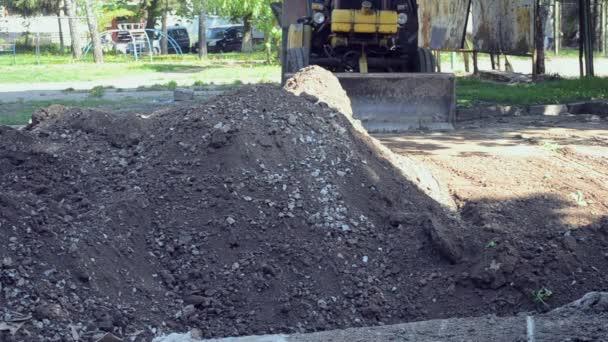 Traktor odstraňuje nečistoty půdy, kopat díry staveniště.