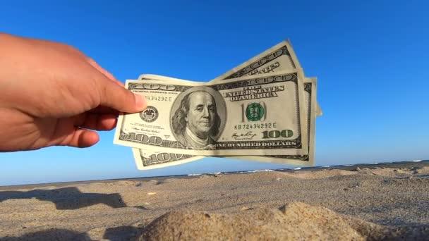 Girl holding money bill of 300 dollars on background of blue sky