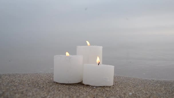 Three small white paraffin candles burning on sandy beach shore edge