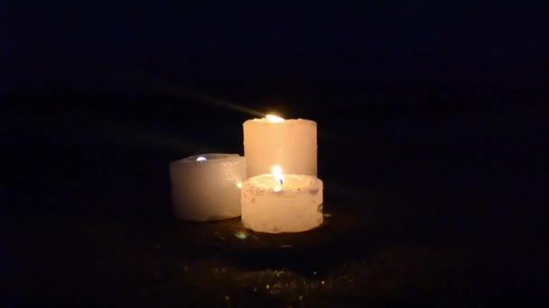 Three small yellow candles on sandy beach near sea ocean waves
