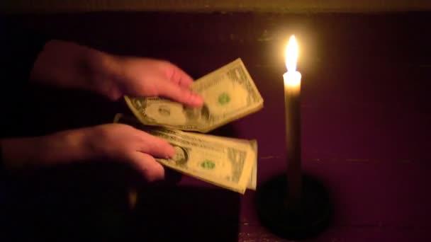 Mann zählt bei Kerzenschein im Dunkeln Dollarscheine