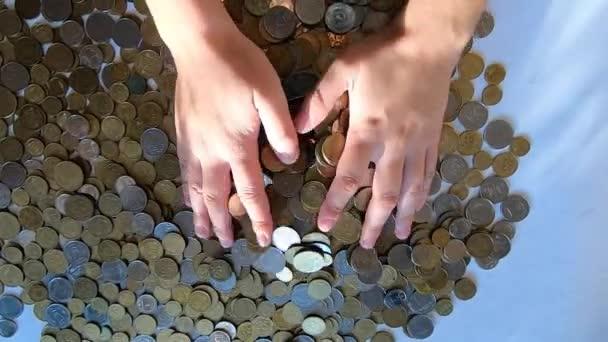 Személy két kéz gereblye érmék az asztalra, és ömlött a maroknyi a felszínre