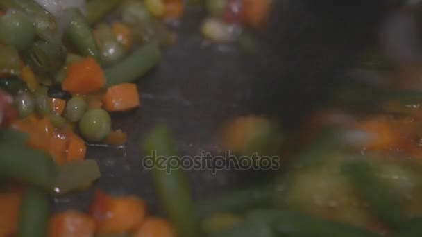 Closeup of human in kitchen cooking stir fry frozen vegetables hd footage slow motion