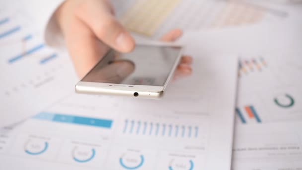 Man Using Mobile Phone on table background with Graph Money Stock Trading Up charts, Business Economic Concept footage