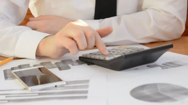 Close up of a businessman hands working in calculator at office desk and analyzing graphs