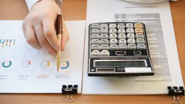 Close up of businessman or accountant hand holding pen working on calculator to calculate business data stock markets trends