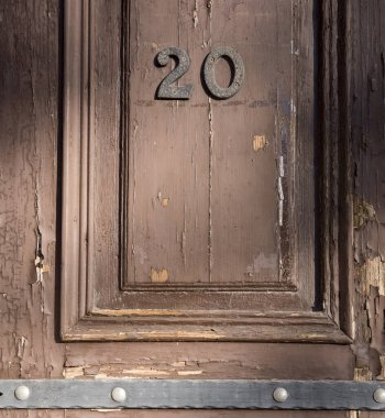 Wooden door made of old textured wood with iron forged stripes. Evening sunny weather, soft light. The door is painted brown, ragged. On the door hangs the numbers 20 indicating the apartment number.
