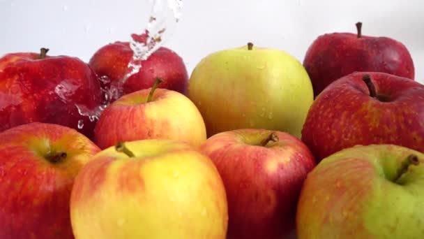 Mytí jablek pod proudem vody. Zpomalený pohyb.