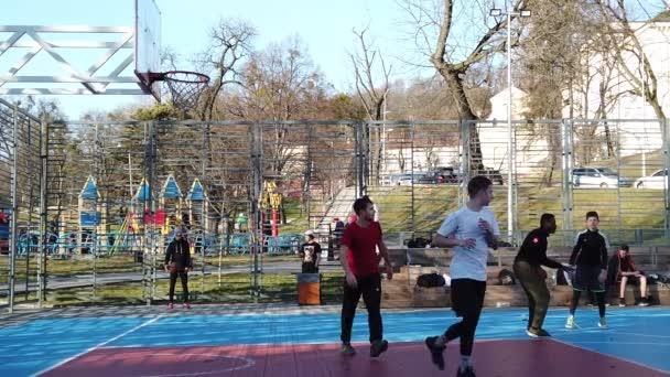 Lviv, Ukraine - 22. Februar 2020: Jugendliche spielen Basketball auf dem städtischen Sportplatz auf dem öffentlichen Platz.