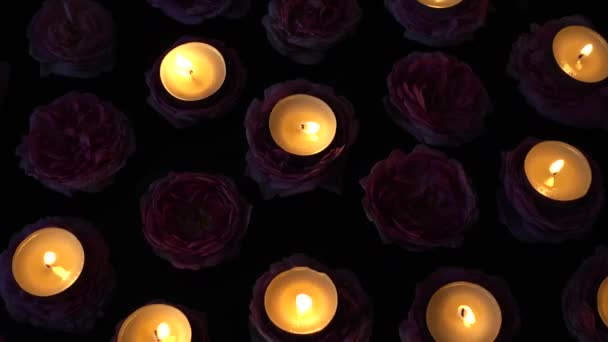 Roses and candles on a black background.