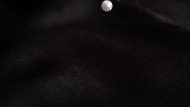 White pearls fall on black fabric. Slow motion.