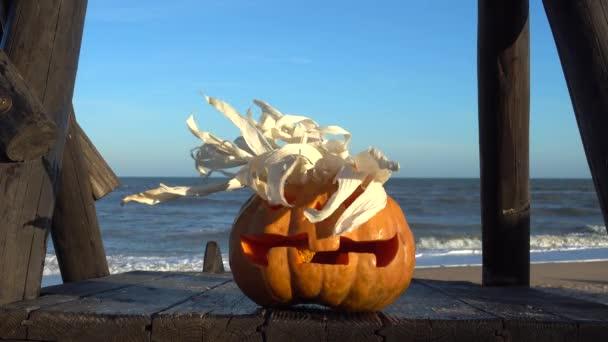 Strašidelná halloweenská dýně. Střílení na pozadí moře. Moře a vlny. Natáčení v říjnu.