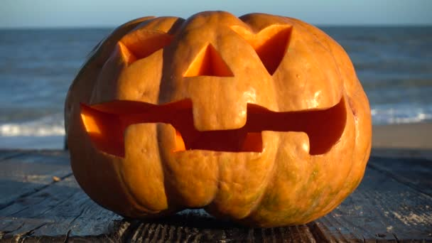 Spooky halloween pumpkin. Shooting against the background of the sea. Sea and waves. Shooting in October.