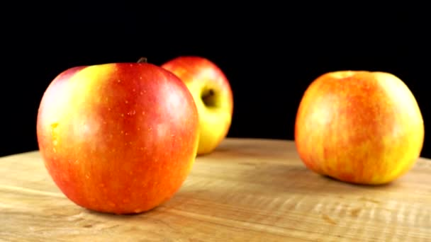 Apples on a black background. Cutting board in the movement.