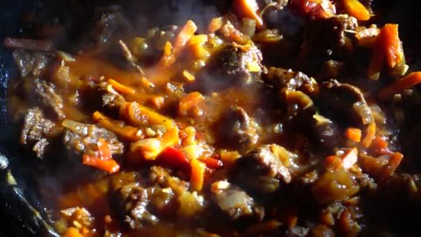 Proces přípravy guláše se zeleninou na pánvi z vepřového železa. Zpomalený pohyb.