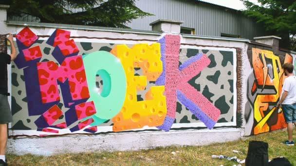 A művészek graffitit rajzolnak a kerítésre. Absztrakt rajz.
