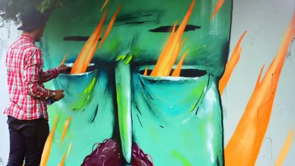 A művész graffitit rajzol a kerítésre. Absztrakt rajz.