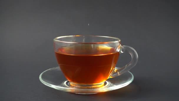 Cukor beleesik egy csésze teába. Lassú mozgás..