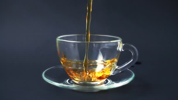 Tea is poured into the cup.Slow motion.