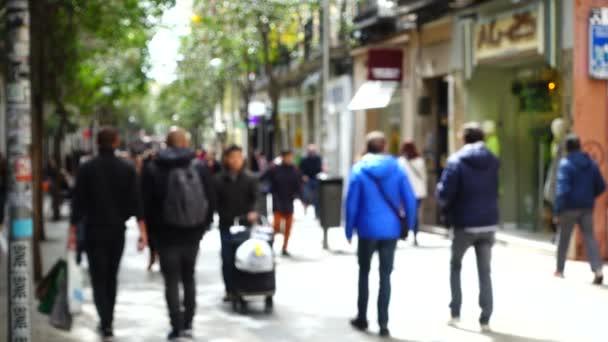 Menschen auf den Straßen Madrids. Aus dem Fokus geraten. Zeitlupe. Bewegung der Menschen entlang der Straße Fuencarral.