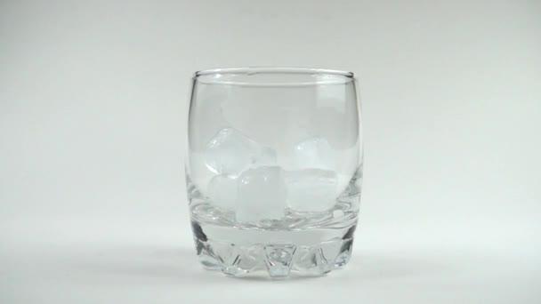 Kostky ledu padají do sklenice. Zpomal. 240 fps. Zpomalený pohyb.