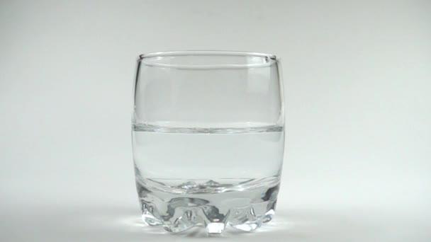 Kostky ledu padají do sklenice s vodou. Zpomal. 480 fps. Zpomalený pohyb.