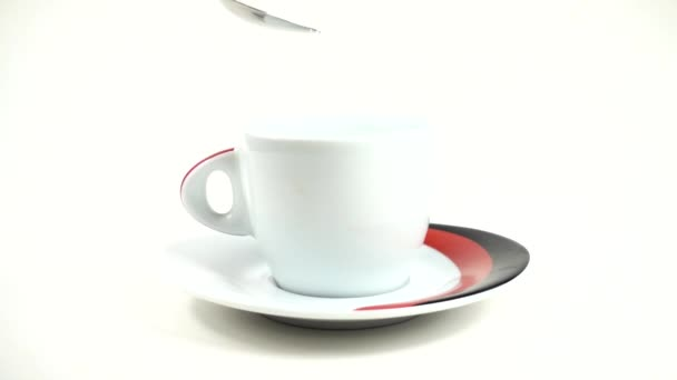 From a spoon sugar is filled in a cup. Slow motion. 240 fps. Slow motion.