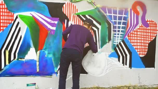 Der Künstler zeichnet Graffiti auf einen Zaun. Graffiti an Zaun.