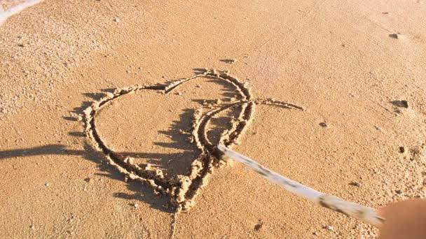 A rajzoló szív a homokon. Lövöldözés a parton.