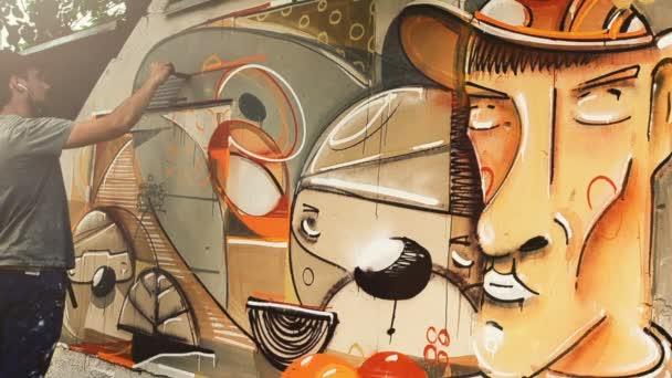 Umělec kreslí graffiti na plot. Graffiti na plotě.