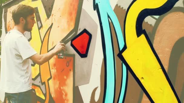 A művész graffitit rajzol a kerítésre. Graffiti a kerítésen.