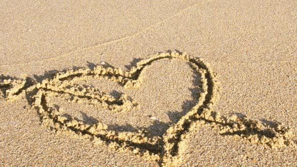 Das zeichnende Herz auf Sand. Das Herz wird von einer Meereswelle weggespült. Schießen am Strand.