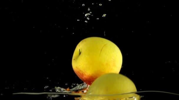 Jablka ve vodě. Zpomalený pohyb.