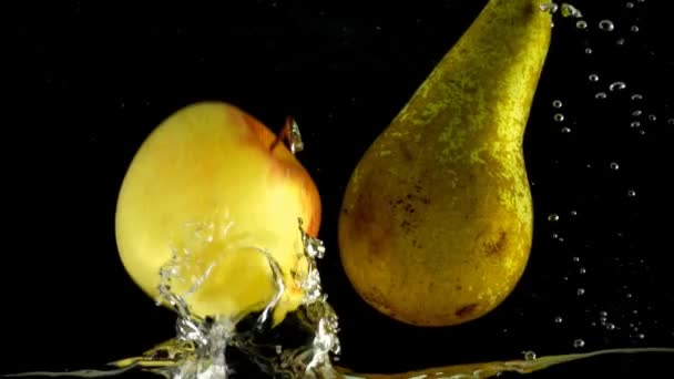 Hrušky a jablka ve vodě. Zpomalený pohyb.