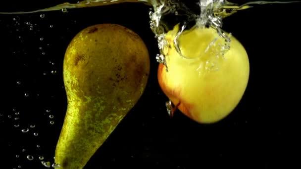 Hrušky a jablka padají do vody. Zpomalený pohyb.