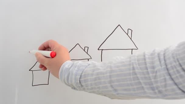 Wir zeichnen Häuser auf eine Tafel mit einem Marker. Wir schreiben mit einem Marker.