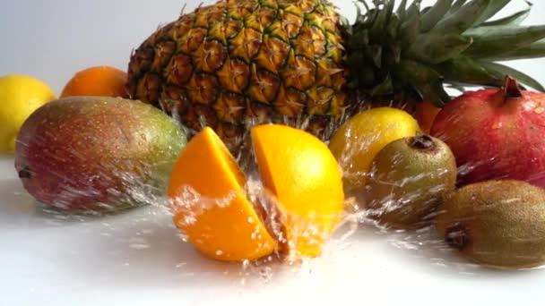 Pád pomeranče na pozadí tropického ovoce. Zpomalený pohyb.