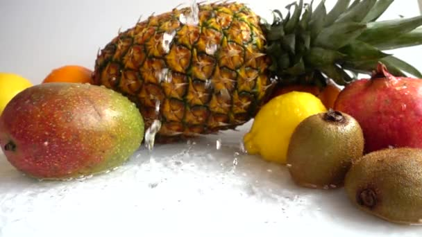 Fall of orange against the background of tropical fruits. Slow motion.