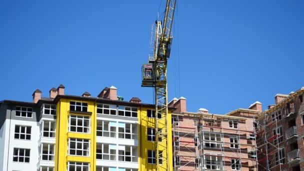 Stavební jeřáby nad domy. Fotografování výstavby domu.
