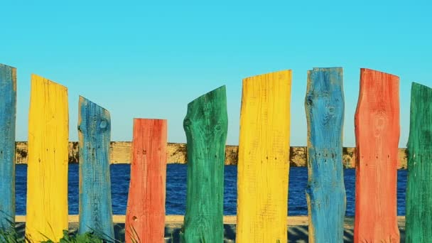 Multi-colored fence against the sea. Shooting of a fence.