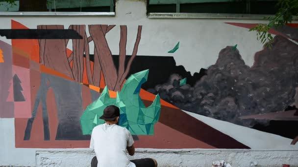 Graffiti, kerítés készítésének folyamata. A művész graffitit rajzol.