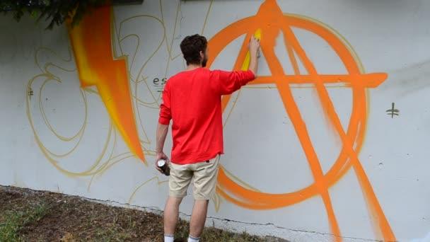 Umělec kreslí graffiti na plot, abstrakce.