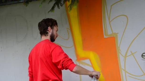 Der Künstler zeichnet Graffiti auf einen Zaun, Abstraktion.