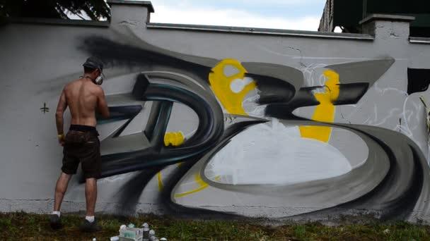 Umělec kreslí graffiti na plot.
