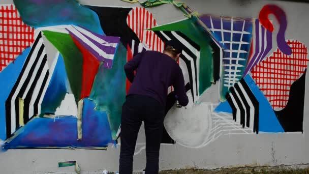 Proces vytváření graffiti, plot. Umělec kreslí graffiti